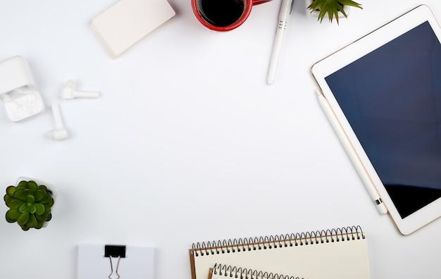 전자 태블릿, 빈 명함, 커피 한잔과 무선 헤드폰 화이트 테이블