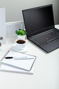 원격 작업 또는 연구를위한 노트북이있는 흰색 테이블. 회색 배경에 빈 디스플레이 레이아웃 템플릿과 함께 검은 노트북. 홈 인테리어의 사무실 pc 책상 작업 공간.