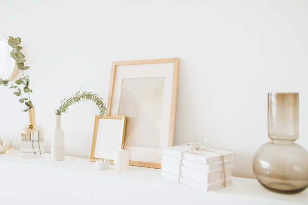 White table with photo frame, gift box, vase, eucalyptus at white wall