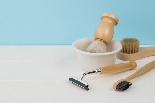 A white table with shaving accessories on a blue background. space for the text.