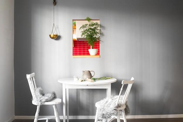 멋진 인테리어와 벽에 그림이있는 방에 두 개의 의자가있는 흰색 테이블