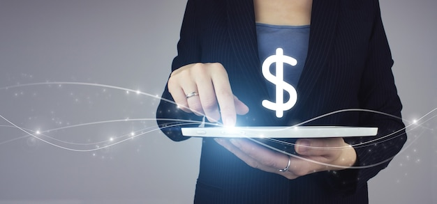 White tablet in businesswoman hand with digital hologram glowing dollar sign on grey background. business. finance. wealth.