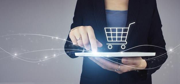 灰色の背景にデジタルホログラムショッピングカートアイコンサインと実業家の手の白いタブレット。オンラインデジタルマーケティング。