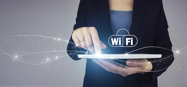 Белая таблетка в руке коммерсантки с цифровым знаком wi-fi голограммы на серой предпосылке. концепция интернет технологии сигнала беспроводной сети wi-fi.