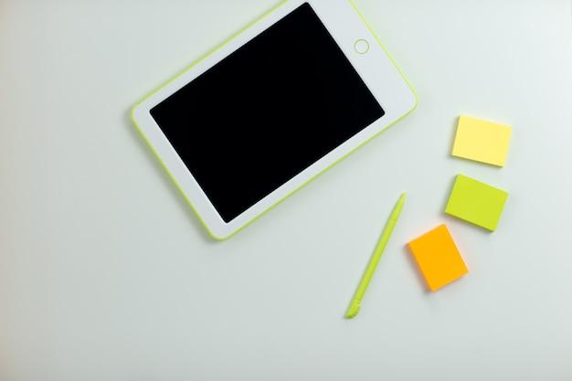 ペンと白いテーブルに付箋で白いタブレット。自宅から仕事をしながら自己分離しながらホームオフィス。検疫中のオンライン教育、eラーニング。
