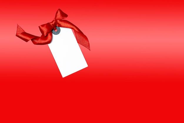 Белая бирка с красным бантом на красном фоне