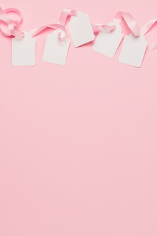 White tags and pink ribbon at the top of the background with space for text
