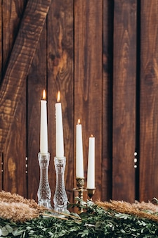 White tall candles in crystal candlesticks on  rustic wooden textured background.