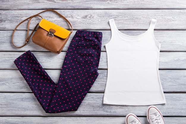 White tank top and pants. dark dotted trousers and bag. girl's summer clothes with purse. stylish casual look.