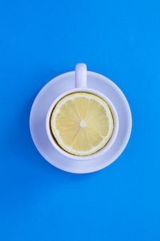 青い表面の真ん中に新鮮な半分レモンが入ったホワイトティーカップ。上面図。スペースをコピーします。創作料理のコラージュ。垂直方向の場所。
