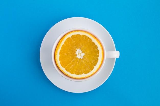 青い背景の真ん中に新鮮な半分にされたオレンジのホワイトティーカップ。上面図。スペースをコピーします。創作料理のコラージュ。