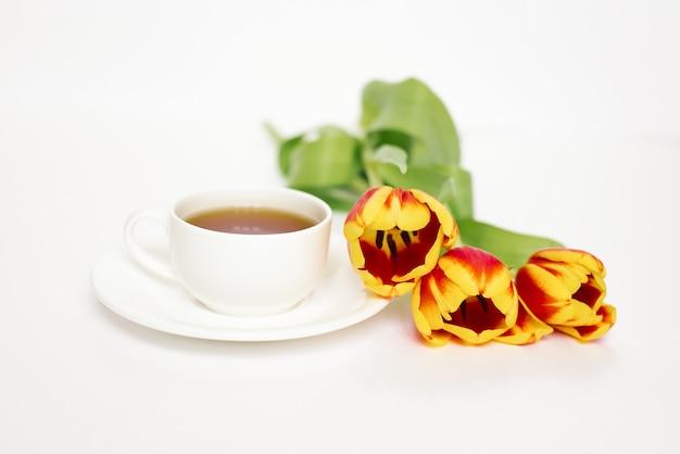 Белая чашка чая с блюдцем и красными и желтыми тюльпанами на белом столе. понятие о любви и весне.