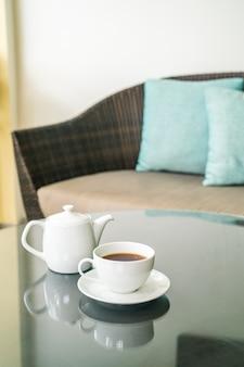 Чашка белого чая с чайником на столе