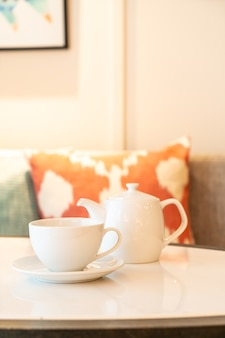 White tea cup with teapot on table