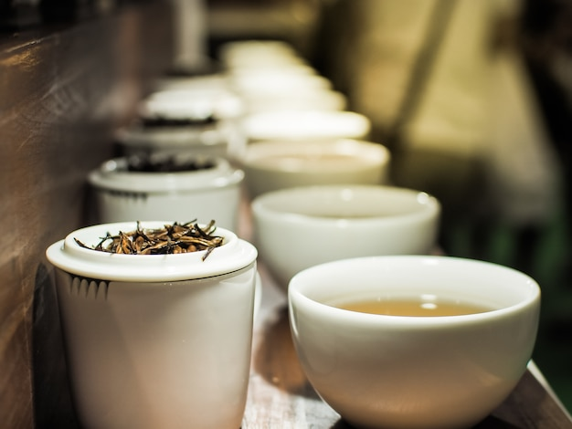 White tea pot and cups with the black tea leaves