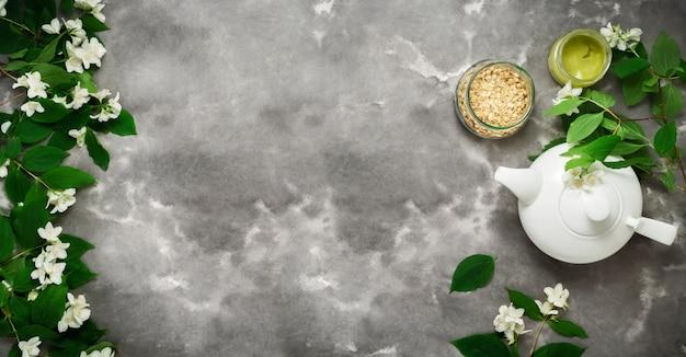 White tea pot, herbal dry tea, jasmin blossom, black white marble flat lay. tea time top view template long web banner