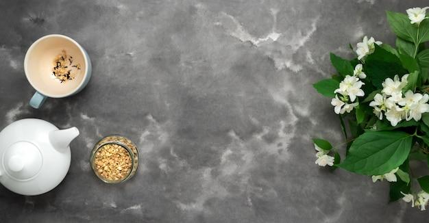 ホワイトティーポット、ハーブの乾燥茶、ジャスミンの花、カップ、黒白い大理石の背景フラットが横たわっていた。ティータイムの長いウェブバナー