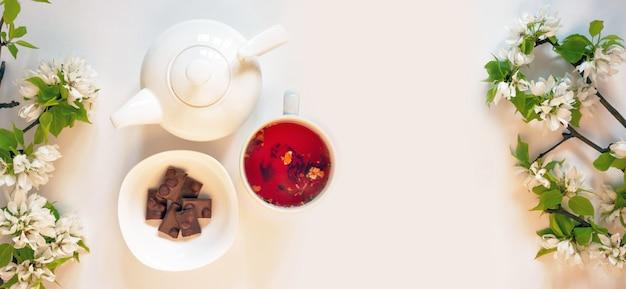 Белый чайник, красный фруктовый чай, шоколад, яблоневый цвет, белая настенная квартира. концепция цветочные весенние цветы