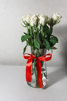 White tea roses stand in a glass vase, which is tied with a red ribbon and stands on the table.