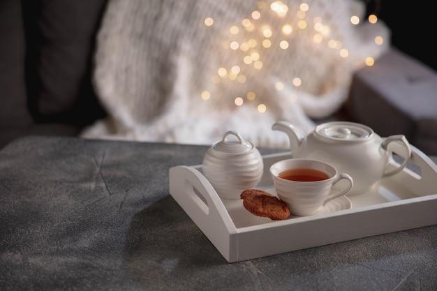 白いティーセットと木製の灰色のテーブルの上のケーキ。カップ、ティーポット、ガーランドライト付きの白い木製トレイ。家の雰囲気、ロマンチックな日付、冬、家の快適さ、クリスマスまたは新年の概念。