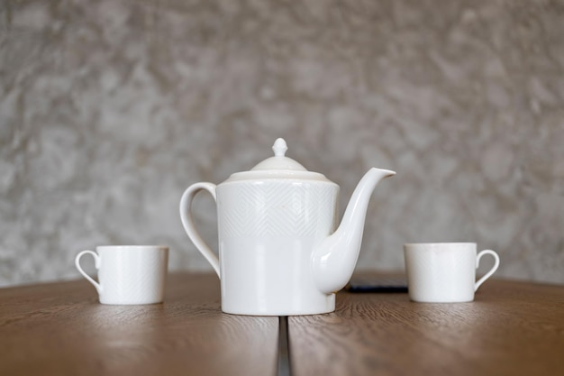 White tea set teapot and two cups stand on a brown table