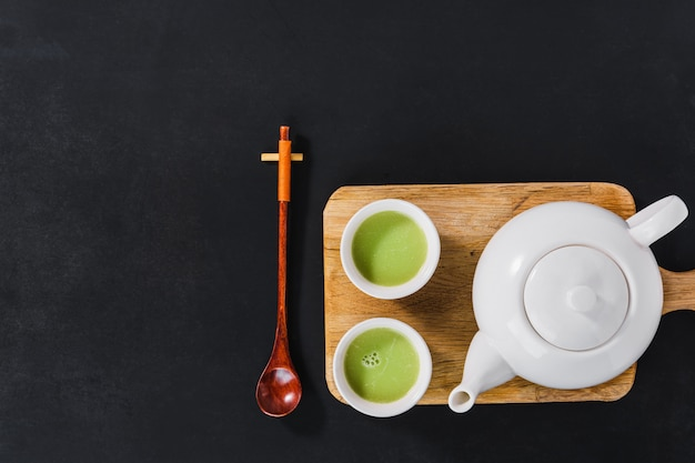 White tea set on wooden cutting board, top view
