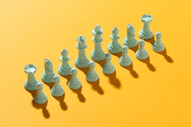 Белые командные шахматы на желтом фоне