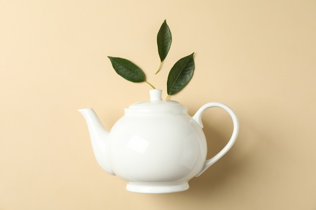 White teapot and leaves on color, space for text