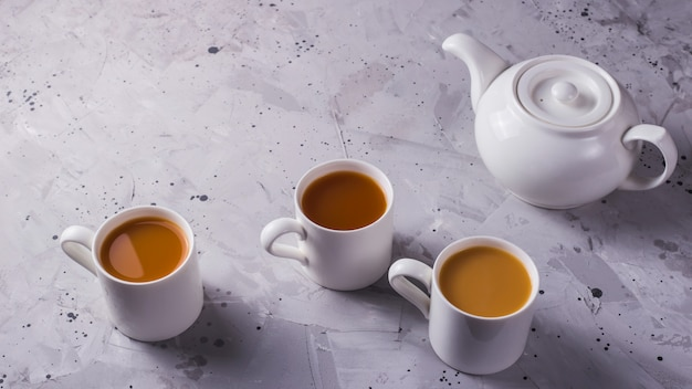 White teapot and white cups of tea or coffee on a gray table
