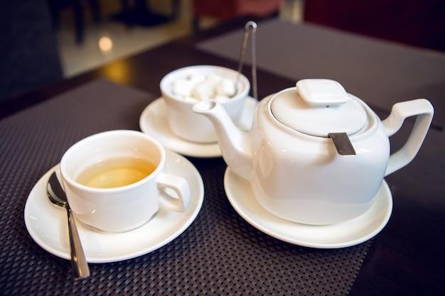 Белый чайник с чашкой чая, блюдцем и чайной ложкой, сахарницей находятся на столе