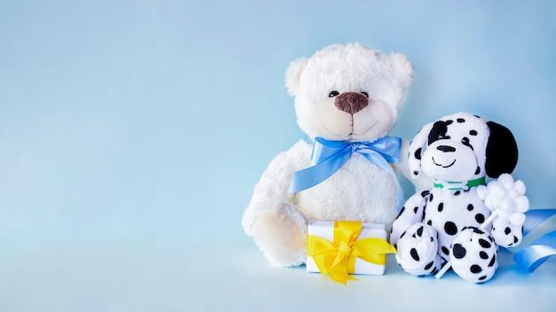 밝은 파란색 배경에 노란색 리본이 달린 작은 선물이 있는 흰색 테디베어와 점박이 개