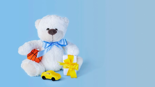White teddy bear holding a  tiny ball small present and toy car on light blue background