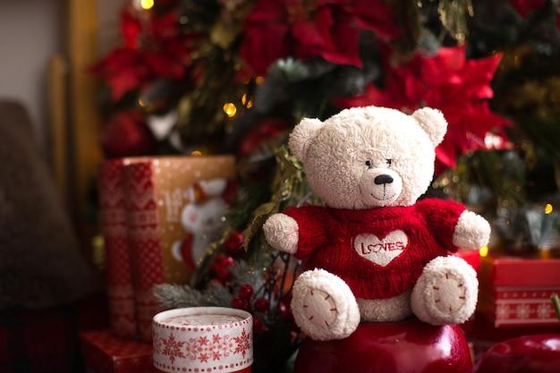 Белый плюшевый мишка в красном вязаном свитере с сердцем на груди и надписью love возле елки