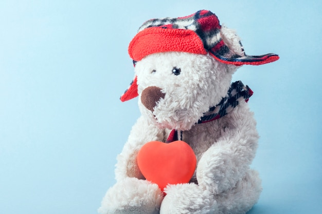 White teddy bear in a red cap with earflaps with a red heart. valentine's day concept, medical concept.