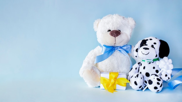 White teddy bear and spotted dog with small present with yellow ribbon on light blue background