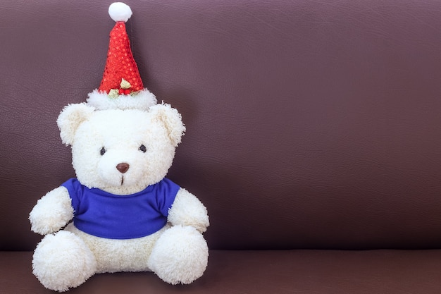 White teddy bear with blue shirt wearing christmas hat on the sofa