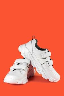 フィットネスやスポーツ、垂直方向の画像のための色付きの背景に白い十代のスタイリッシュなスニーカー