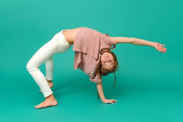 白いズボンとピンクのシャツを着た白い10代の少女は、緑の表面、アクロバットの橋のポーズで立っています