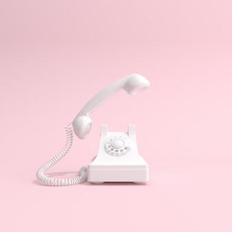 White telephone on pink background