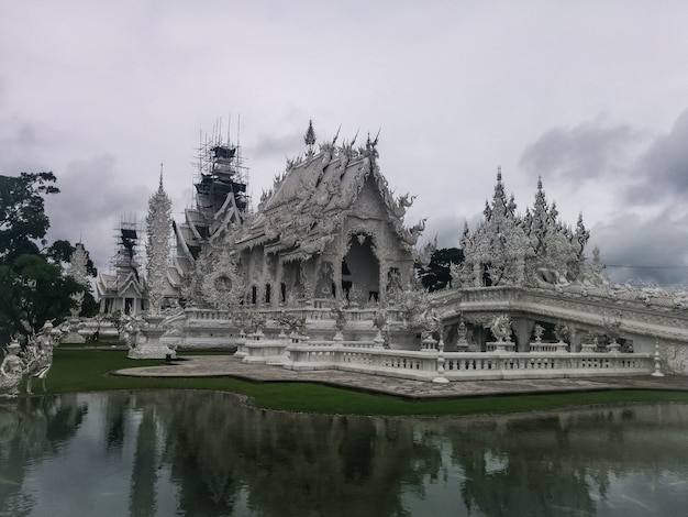 White temple in thailand with some reflections during an overcast day