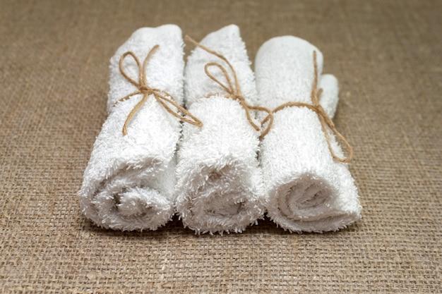 リネン黄麻布の袋に巻かれた白いテリー綿タオル。スパ、サウナ、健康的なライフスタイルのコンセプト。閉じる。選択的なソフトフォーカス。 。テキストコピースペース。
