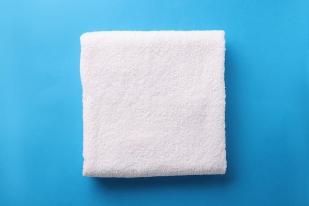 흰색 테리 수건은 파란색 배경에 접혀