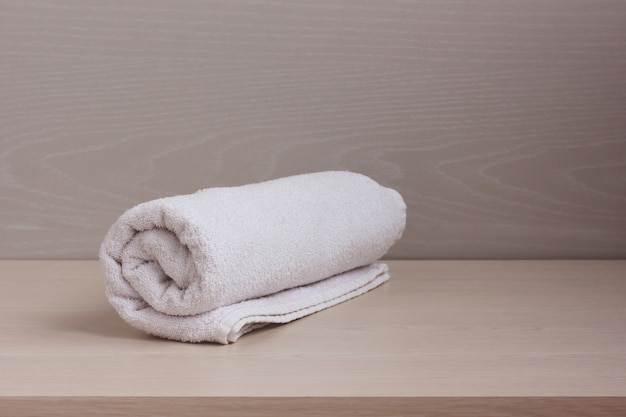 White terry towel in a roll on the shelf.