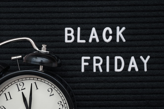 White text black friday on black letter board and alarm clock , closeup.  black friday , season sales time.