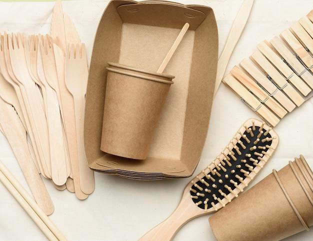 Белый текстильный мешок и одноразовая посуда из коричневой крафт-бумаги на зеленом фоне. вид сверху, концепция отказа от пластика, нулевые отходы