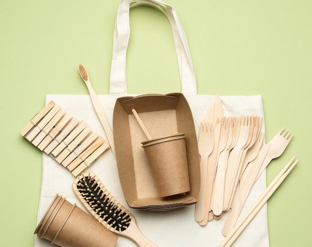 흰색 섬유 가방 및 녹색 배경에 갈색 공예 종이에서 일회용 식기.