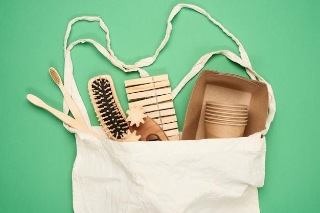 Белый текстильный мешок и одноразовая посуда из крафт-бумаги коричневого цвета, зубные щетки и расческа