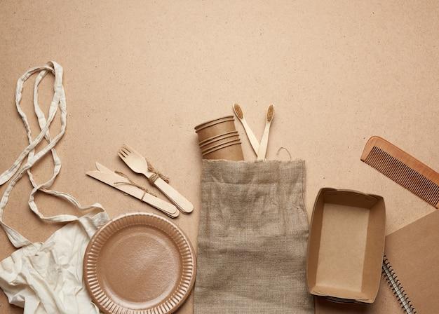 Белая текстильная сумка и одноразовая посуда из коричневой крафт-бумаги