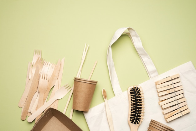 White textile bag and disposable tableware from brown craft paper on a green background. view from above, plastic rejection concept, zero waste