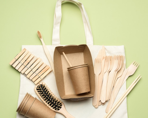White textile bag and disposable tableware from brown craft paper on a green background.